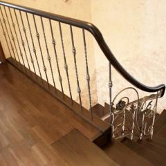 Кованые балясины и гнутый поручень в ограждении лестницы