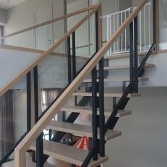 Лестница на металлическом косоуре с ограждением из каленого стекла